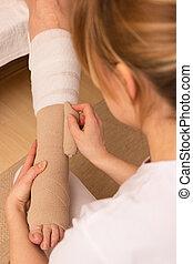 Applying a pressure bandage - A nurse is applying a pressure...