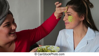 Close-up of a small group of female friends sitting indoors enjoying a girls night in, they are applying an avocado mask to a young adults face.