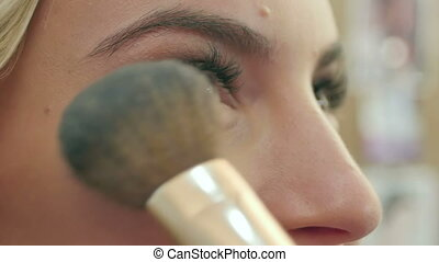 Applying blush makeup with brush to cheekbones of young woman