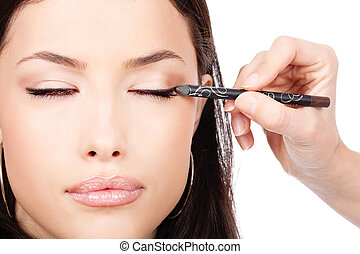 applying cosmetic pencil on closed eye, isolated on white...