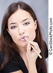 cosmetic pencil on woman's lips, focus on lips