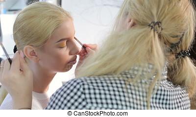 Applying cosmetics to beautiful model. Beauty and fashion
