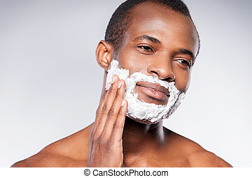 Applying cream on face. Handsome shirtless African man shaving his face and looking at camera while standing against grey background