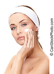 Beautiful young woman applying a creme on her face isolated on white background