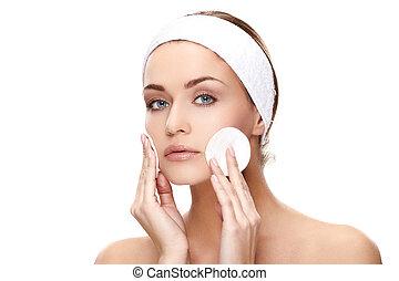 Applying creme - Beautiful young woman applying a creme on ...