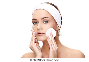 Applying creme - Beautiful young woman applying a creme on...
