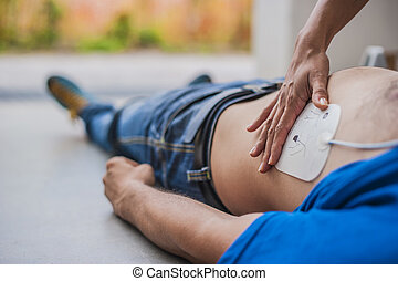 rescuer applying defibrillation pad for saving a life