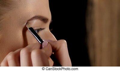 Applying eyebrow brush. Makeup. Black. Closeup