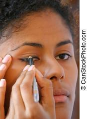 Applying eyeliner - Attractive brazilian girl applying...
