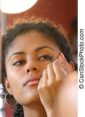 Applying eyeliner - Beautiful brazilian girl applying...