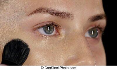 Applying foundation on the face. Black. Closeup