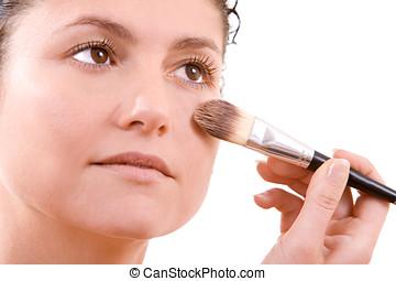 Applying foundation - Beautiful brunette applying foundation...