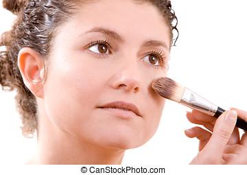 Applying foundation - Pretty brunette applying foundation...