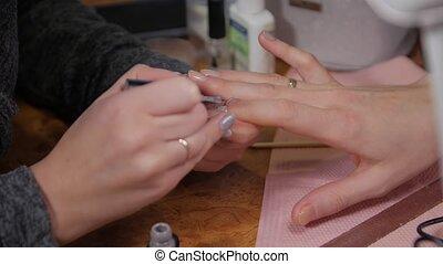 Applying gray nail polish woman hands closeup