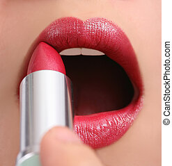 Applying lipstick - Beautiful girl applying red lipstick,...