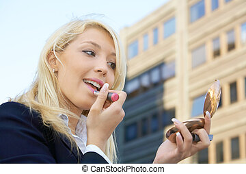 Applying Lipstick - Businesswoman applying lipstick outdoors...