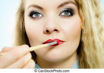 Applying lipstick on fashion model lips