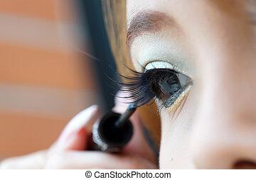 Applying liquid eyeliner with brush, close up