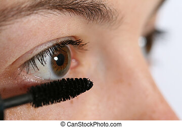 Applying mascara - closeup of a woman applying mascara
