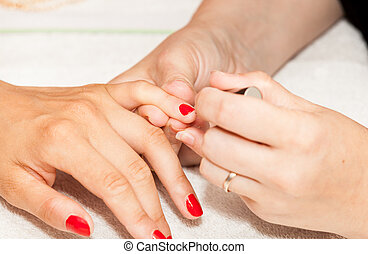 Applying nail polish on a woman's hands