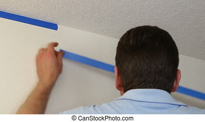 Applying Painter's Tape - Man preparing to paint ceiling by...