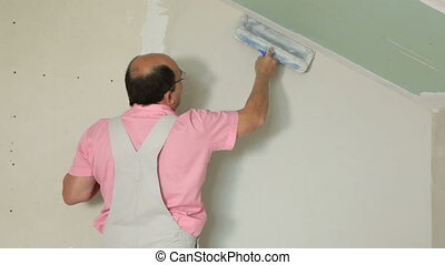 Applying Plaster to Plasterboard Wa - Man applying plaster...