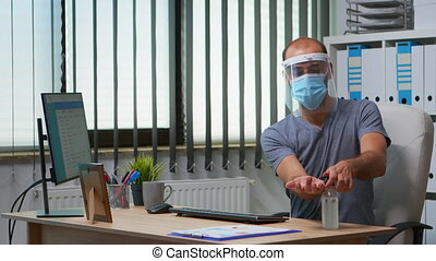 Man with protection mask and visor applying sanitizer gel rubbing hands before working at computer. Entrepreneur in new normal workplace disinfecting using antibacterial alcohol against corona virus.