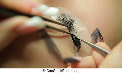 Applying the false eyelashes to model - Make-up artist...