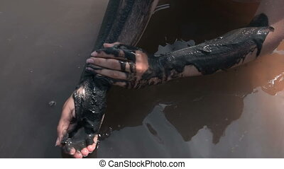Applying therapeutic mud from salty lake - Young woman...