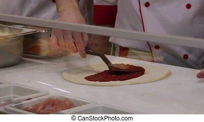 Applying tomato sauce on original Italian raw pizza, dough...