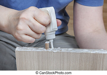 Applying wood glue, carpenter gluing wooden parts for furniture, close-up.