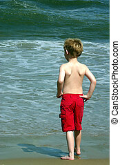A little boy apprehensive about getting into the water.