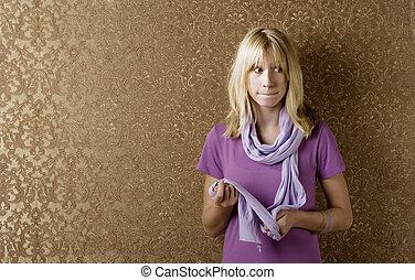 Apprehensive young girl leaning against a wall with gold...