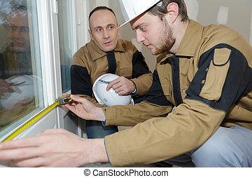 apprentice construction man using tape measurer at site
