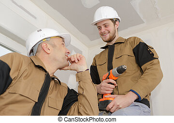 apprentice construction worker at site with instructor