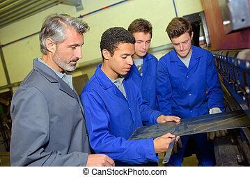 Apprentice measuring a piece of flat metal