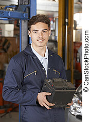 Apprentice Mechanic Holding Car Battery In Auto Repair Shop