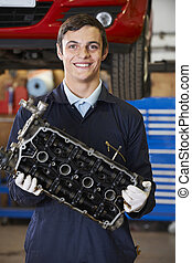 Apprentice Mechanic Holding Engine Block