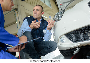 apprentice mechanician working on car with teacher