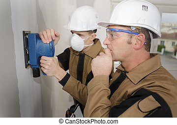 apprentice sanding of a wall with a power sander