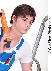 Apprentice workman with a spirit level
