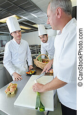 apprentices cooks watching the chef garnishing a dish