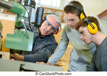 apprentices learning to use industrial machine