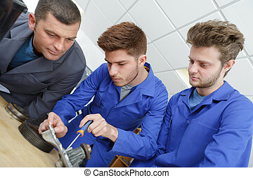 Apprentices working on metal part with screwdriver
