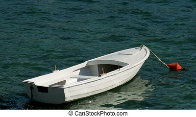 approached a white wooden boat with orange buoy in the water...