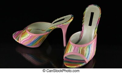 Approaching, a pair of pink clogs standing on a black ...