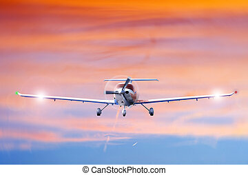 Approaching propeller aircraft seen from the front, against a vivid, radiant sky