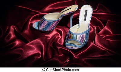 Approaching, pair of blue clogs with high heels standing on a red cloth. Zoom