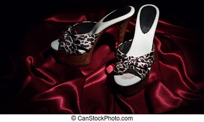 Approaching, pair of leopard clogs with high heels standing on a red cloth. Zoom