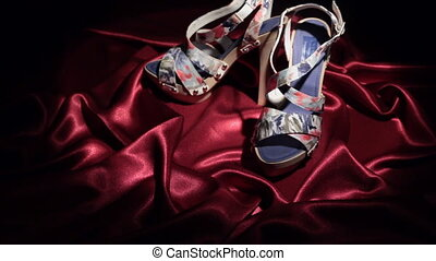 Approaching, pair of pair of blue high-heeled sandals standing on a red cloth. Zoom